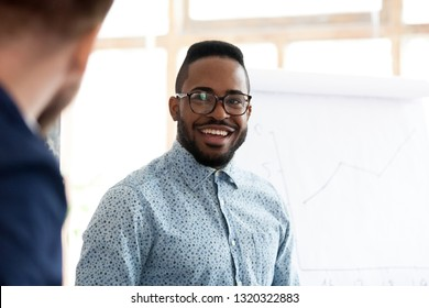 Diverse employees standing and talking, focus on african mixed race male. Head shot portrait smiling american manager in eyeglasses chatting with colleague or company corporate client caucasian man
