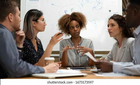 Diverse employees team with African American businesswoman leader discussing project statistics at briefing, sitting at table in boardroom, business partners sharing startup ideas at meeting