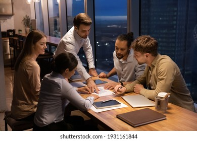 Diverse employees working with financial project statistics at late meeting in office, confident businessman executive pointing at document with diagrams and charts, multiracial team brainstorming