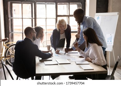 Diverse employees working with project documents at meeting in boardroom, sitting at table, analyzing statistics, reading financial report, colleagues engaged in teamwork at corporate briefing