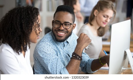 Diverse employees working in shared office, focus on black smiling male talking flirting with colleague sitting at desk using pc. Mentor provide information to trainee having friendly good relations