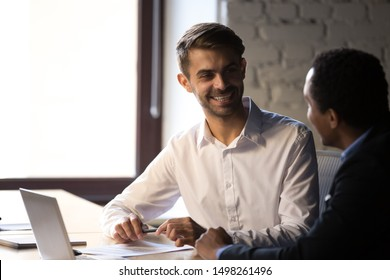 Diverse employees working together, discussing project, business strategy, smiling Caucasian worker talking with African American colleague, having pleasant conversation during break at work