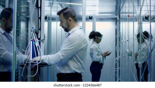 Diverse engineers work in the server room in the data center with cables