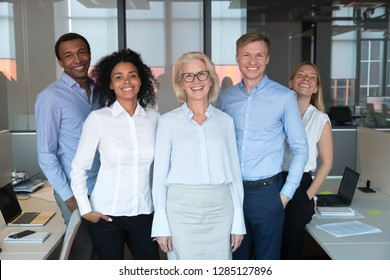 Diverse excited happy company members standing posing for photo, successful employees led by middle aged female chief or executive manager portrait, people feels satisfaction of the work done concept