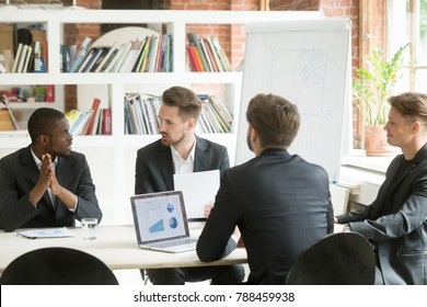 Diverse executive business team discussing work results at meeting, multiracial businessmen talking analyzing financial statistics report sitting together in modern office with laptops and documents