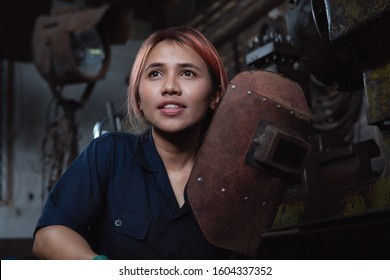 Diverse female industrial engineer holding welding helmet after work shift - Young Asian factory metal worker taking a break - Hispanic apprentice woman learning new skills on internship training
