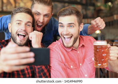 Diverse football fans watching football on smartphone and celebrating victory score in pub.