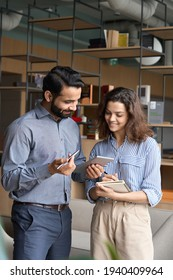 Diverse friendly coworkers talking using digital tablet in office. Indian manager having discussion with latin employee meeting in office lobby discussing project, teaching new employee sharing ideas. - Shutterstock ID 1940409964