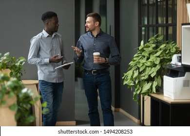Diverse friendly male partners colleagues talking walking in modern office hallway, young african american and caucasian business men discussing common project work meeting in company work space