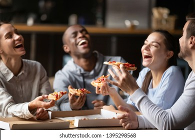 Diverse friends eating pizza, happy colleagues or students having fun together in cafe, men and women laughing at funny joke, holding Italian junk food slices in hands at meeting in cafeteria