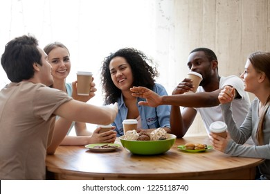 Diverse friends girls and guys sitting around table chatting having fun drink coffee in paper cups enjoy time together. Friendship between different race multinational young millennial people concept