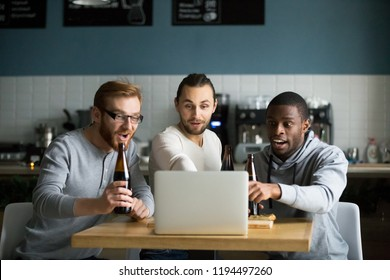 Diverse friends hang out in café drinking beer, watching online game at laptop, multiethnic males cheering football team enjoying match sitting in pub, guys have drinks hanging out in bar