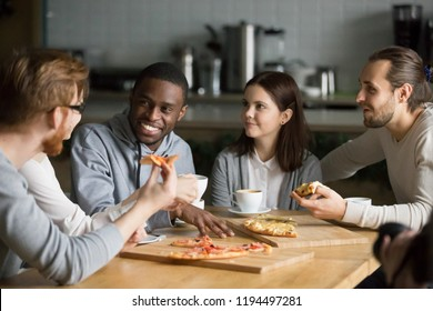 Diverse friends have fun meeting in pizzeria for lunch, multiethnic colleagues eat pizza talking and discussing news in Italian restaurant, young people speak resting in café, hanging out together