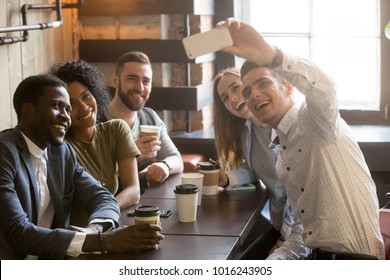 Diverse friends making selfie on smartphone together in cafe, young man holding phone shooting video or taking photo on mobile of african and caucasian millennial people sitting at coffee shop table