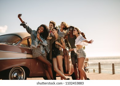 Diverse friends on road trip taking selfie with mobile phone. Group of men and women taking self portrait outdoors by the car.