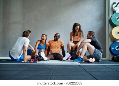 Diverse friends in sportswear talking and laughing together while sitting on the floor of a gym after a workout