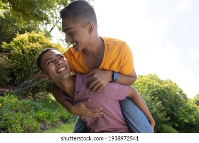 Diverse gay male couple spending time in garden embracing and smiling. staying at home in isolation during quarantine lockdown.