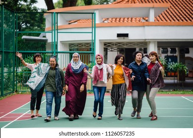 A diverse group of Asian women (Malay and Chinese) walking together side by side in a basketball court. They are friends and they are goofing around and striking poses and smiling as they walk.