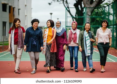 A diverse group of Asian women (Malay and Chinese) walk side by side in a basketball court and are laughing as they walk.