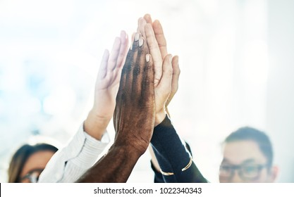 Diverse group of business colleagues high fiving each other while standing in a huddle together in a bright modern office