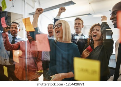 Diverse group of businesspeople cheering and fist pumping while brainstorming together with sticky notes on a glass wall in an office