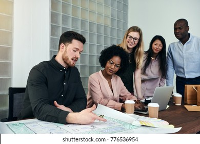 Diverse group of businesspeople discussing building blueprints while working together around a table in a modern office