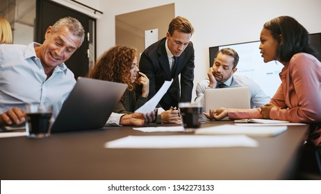 Diverse group of businesspeople sitting around a table in an office boardroom discussing paperwork together