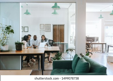 Diverse group of businesspeople sitting together around a table inside of a glass office boardroom and working on a laptop