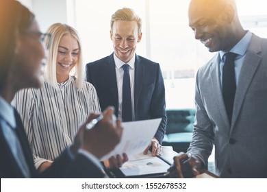 Diverse group of businesspeople smiling during a meeting together around a table in an office