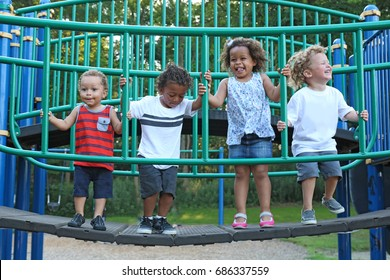a diverse group of children are playing together on the playground equipment. The kids are of difference races, including African American, hispanic and white. The happy children are jumping
