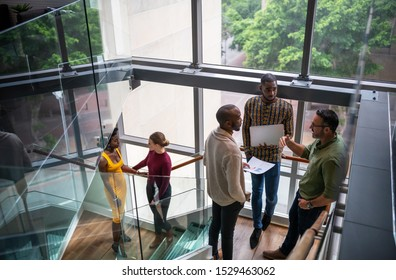 Diverse group of creative business people casually talking on office stairwell before meeting