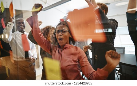 Diverse group of ecstatic businesspeople cheering together over a winning idea while brainstorming with sticky notes on a glass wall in a modern office