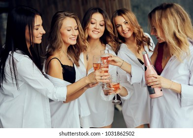 Diverse group of female friends enjoying at a party and laughing  with glasses of champagne. Group of beautiful women having fun. Beautiful ladies  in white clothes
