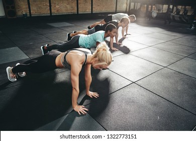 Diverse group of fit people in sportswear doing pushups on the floor of a gym during an exercise class together