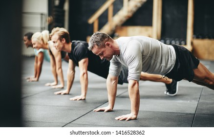 Diverse group of fit people in sportswear doing pushups together on a the floor of a gym during an exercise session