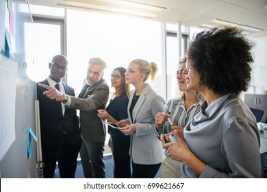 Diverse group of focused work colleagues talking together during a brainstorming session on a whiteboard in a bright modern office