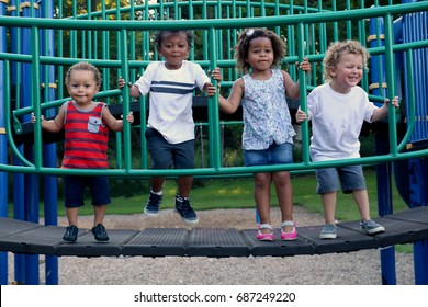 A diverse group of four children are playing together at the park. They are laughing and jumping on a gym. The children are of different races, including African American, Caucasian and Hispanic.