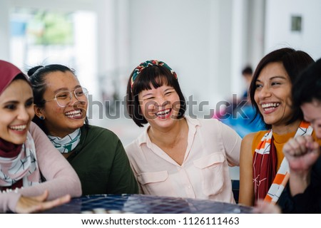 A diverse group of friends chat as they sit around a chess table during the day. The Chinese and Malay women sit and talk and are laughing and smiling as they joke and talk.