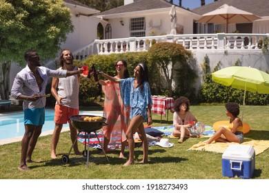 Divers groupes d'amis faisant un barbecue et parlant à une fête de piscine. sortir, boire de la bière, faire un toast et se détendre à l'extérieur en été.