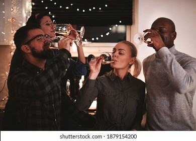 Diverse group of friends sipping from glasses of wine while having fun together at a party