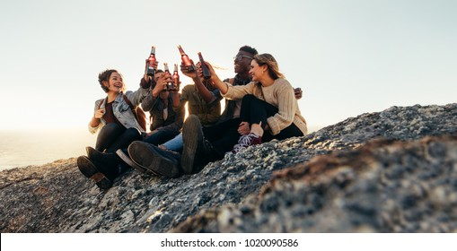 Diverse group of friends sitting on mountain top and toasting beers. Cheerful young men and women enjoying with beers outdoors at sunset.