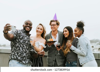 Diverse group of friends taking a selfie at a birthday party