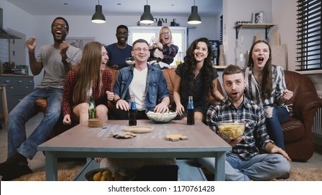 Diverse group of friends watch sports on TV. Backstage camera films happy supporters, fans on couch cheer with snacks 4K
