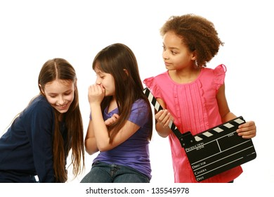 diverse group of girls with one whispering and other holding film slate