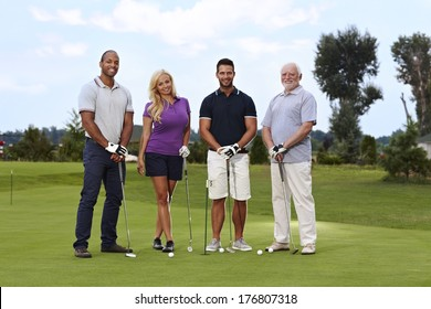 Diverse group of golfers standing on the green, smiling, looking at camera.