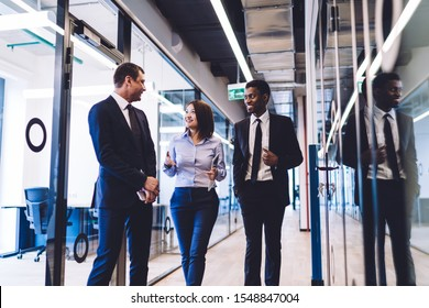 Diverse group of happy successful smiling coworkers wearing formal clothes discussing news and sharing opinions while walking in office corridor