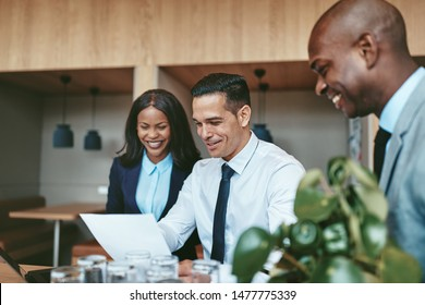 Diverse group of laughing businesspeople working on a laptop and reading paperwork together and at a table in an office