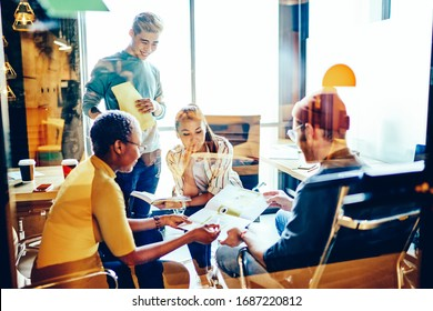 Diverse group of multiracial colleagues enjoying cooperate teamwork for discussing organization plan, millennial hipster creators have distance brainstorming for collaboration in coworking space
