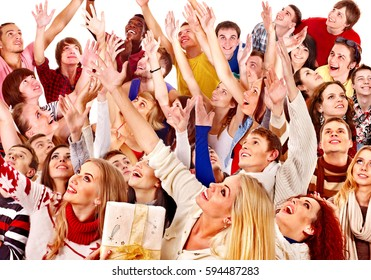 Diverse group of people look up on isolated. Cheering crowd wait sale. Happy and emotional multiethnic men and women raising hands together. Girl holding gift box. Fans meet friends on holiday event.