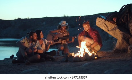 Diverse group of people sitting around bonfire on coast grilling food and playing guitar.